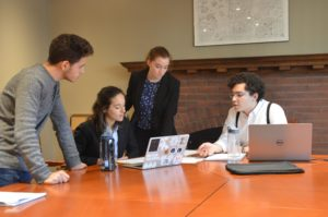 A group of 4 Munk One students stand around a table with chairs discussing ideas for their case competition.