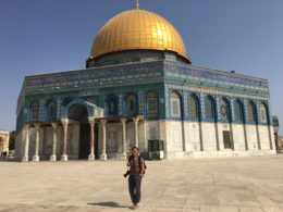 Student stands in front of the famous Temple Mount where the building is bright against a blue sky