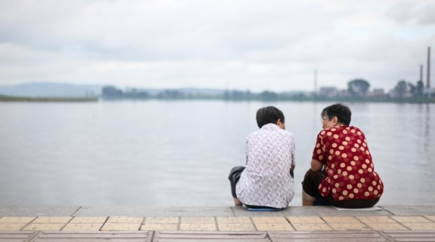 Photo of two women sitting by a lake. Photo by Glen Chua