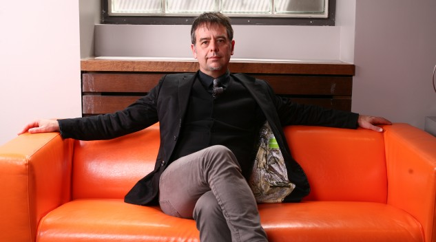 Ron Deibert sitting on an orange couch. Photo by Dave Chan.