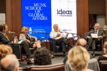 In foreground: Backs of heads of seated audience members. In back, four seated panelists in front of Blue Munk School of GLobal Affairs banner and white CBC Radio Ideas banner.
