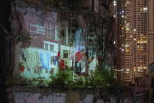 Rectangular art photograph showing collage of urban apartment buildings with a laundry line and human figure in a red shirt in lower left foreground