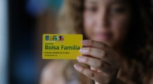 A young woman holds a Bolsa Familia membership card to the foreground.