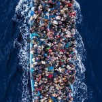 A large boat containing hundreds of people swims in the floats in the middle of the ocean.