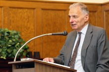 Ralph Nader stands speaking at a lectern.