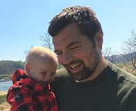 Ryan Hoskins holding a baby.