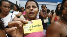 A woman standing in a crowd of people holds up a Bolsa Familia health care card.