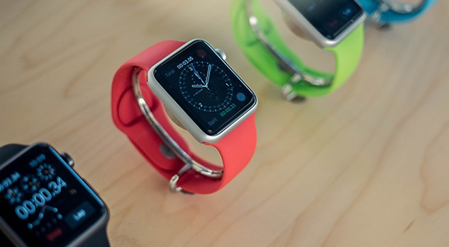 A series of apple watches lined up on a table