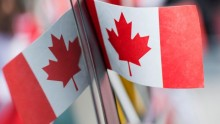 A small Canadian flag against a mirror