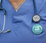Close up of a doctor wearing strike button on their scrubs