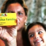 A woman holds a child and a Bolsa Familia card
