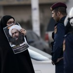A Bahraini woman clashes with riot police after a protest