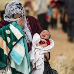 A mother and child cross the border as they flee the Syrian civil war