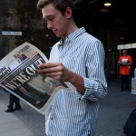 Man stands in the streets of London reading newspaper