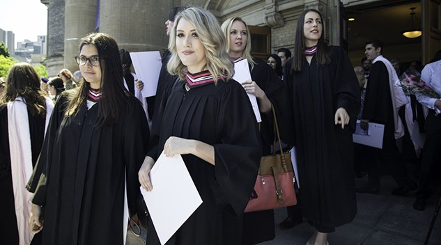 A group of graduates walk out of Convocation Hall