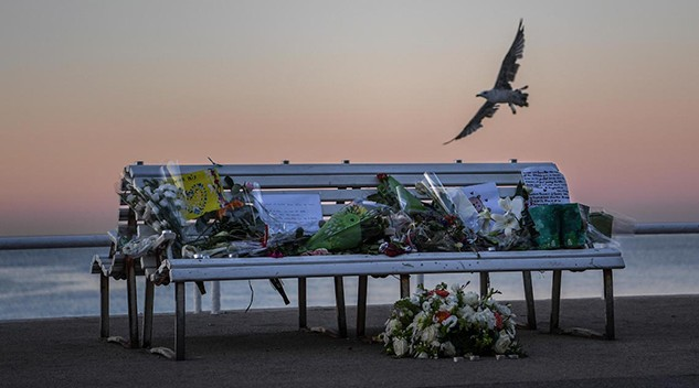 A tribute of flowers is laid on a bench in Nice, France