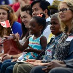 A little girl sits on her cousin's lap waving a Canadian flag.