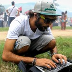A man crouches in the grass with a laptop computer.