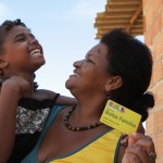 A woman holds a Bolsa Familia benefit card in one hand, and her child in the other
