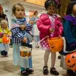 A group of children trick or treat at an indoor office