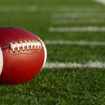 An American football resting on an empty football field