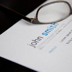 A pair of glasses sits on top of a resume