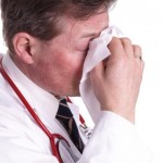 A doctor blows his nose.