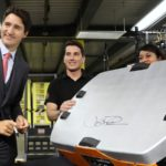 Prime Minister Justin Trudeau signs a robotic unit during a tour of the Amazon Fulfillment Centre in Brampton.