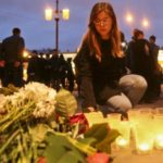 A woman lays flowers at a makeshift memorial