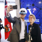 Kathleen Wynne, premier of Ontario, right, poses for a selfie photograph with a man wearing a virtual reality helmet.