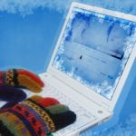 A pair of gloved hands typing on a frozen laptop.