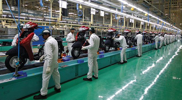 Employees work on an assembly line of Honda Motorcycle & Scooter India.
