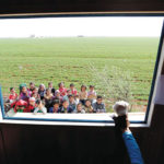 Children watch as a teacher puts on a puppet show inside a mobile education caravan.