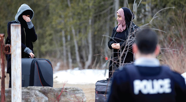 A woman claiming to be from Yemen wipes tears from her eyes as she is told not to cross the U.S.-Canada border.