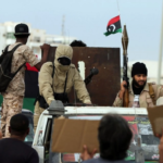 Armed Libyan men wave their national flags during a demonstration marking the fifth anniversary of the Libyan revolution.
