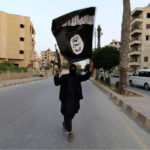 A member loyal to the Islamic State waves the group's flag in the Syrian city of Raqqa.