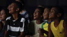 A group of children gather at a documentary screening.