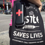 A woman carries a naloxone kit and a bag from Insite, the safe injection site