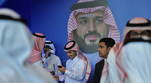 Young Saudis chat by a poster of Saudi Crown Prince Mohammed bin Salman during a tech forum in Riyadh