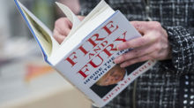 A person stands reading Michael Wolff's book Fire and Fury.