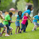 Kids and counselors playing tug of war at summer camp.
