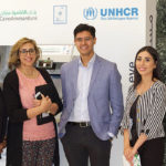 A group of student researchers pose in front of a UNHCR ATM.