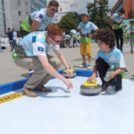 Peter Anderson is pictured teaching a child the basics of curling.