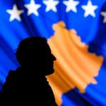 A man stands in front of a screen displaying the Kosovo flag