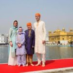 Justin Trudeau, dressed in a gold sherwani, poses with his wife and children.