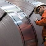 A Dofasco employee looks at rolls of coiled steel