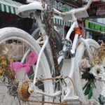 An all-white bike adorned with flowers in a makeshift memorial on a street corner