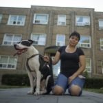 Gabriela Martinez, a Toronto resident, poses in front of her apartment building with her dog.