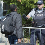 An asylum-seeker is confronted by an RCMP officer as he enters Canada from the United States
