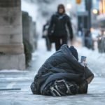 A homeless person sits in the street wrapped in a blanket